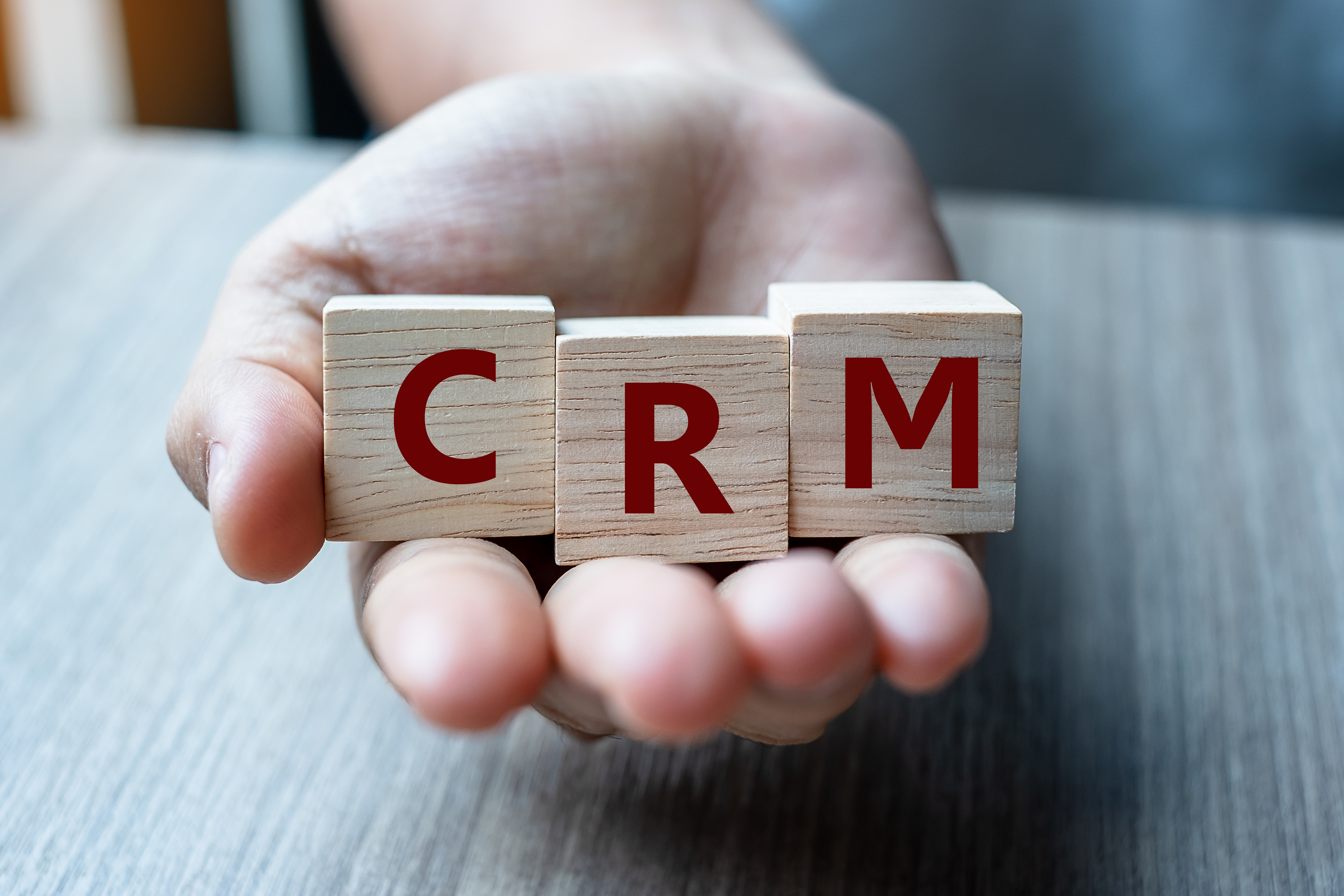 business-woman-hand-holding-wooden-cube-with-crm-t-B7PMTGA-jpg